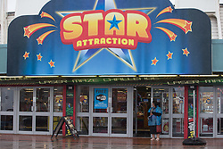 "© Licensed to London News Pictures . 17/06/2015. Blackpool  , UK . A woman in a plastic poncho takes in the doorway of "" Star Attraction "" on Blackpool Promenade . Rain and fog over Blackpool today ( Wednesday 17th June 2015 ) . Photo credit : Joel Goodman/LNP"