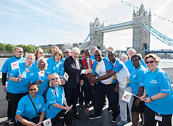 Image ©Licensed to i-Images Picture Agency. 06/06/2014. London, United Kingdom. Mayor of London Boris Johnson holds the Commonwealth Games Queen\'s Baton Relay with Michael Pusey (right), World and Commonwealth champion Christine Ohuruogu MBE (red t-shirt), Faramolu Johnson (far right) and teachers from Alfred Salter Primary School in Rotherhithe to the capital as part of the England led of a journey that will see it travel 190,000 kilometres over 288 days. City Hall, The Queen\'s Walk. Picture by Daniel Leal-Olivas / i-Images