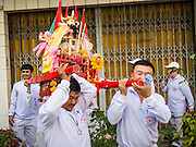 07 FEBRUARY 2014 - HAT YAI, SONGKHLA, THAILAND:  A group of men carry a small altar to a business during Lunar New Year. Groups of men go business to business with small altars and business owners make offerings and pray at the altars.  Hat Yai was originally settled by Chinese immigrants and still has a large ethnic Chinese population. Chinese holidays, especially Lunar New Year (Tet) and the Vegetarian Festival are important citywide holidays.     PHOTO BY JACK KURTZ