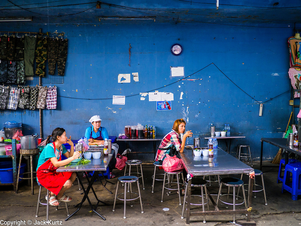 30 MAY 2013 - BANGKOK, THAILAND: People eat in a food stall in Bobae Market in Bangkok. Bobae Market is a 30 year old famous for fashion wholesale and is now very popular with exporters from around the world. Bobae Tower is next to the market and  advertises itself as having 1,300 stalls under one roof and claims to be the largest garment wholesale center in Thailand.     PHOTO BY JACK KURTZ