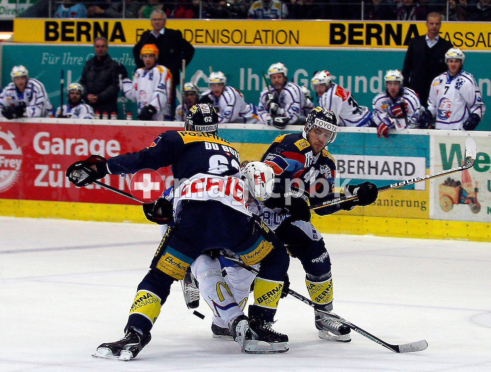 Kloten Flyers defender Felicien Du Bois (L) and forward Matthias Bieber (R) stop ZSC Lions forward Adrian Wichser (C) during ice hockey game five of the Swiss National League A Playoff Quarterfinal between Kloten Flyers and ZSC Lions held at the Kolping Arena in Kloten, Switzerland, Tuesday, March 8, 2011. (Photo by Patrick B. Kraemer / MAGICPBK)