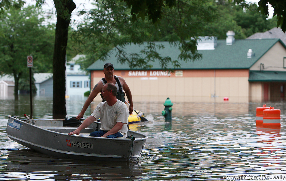 Massive flooding has covered the Midwest section of the United States. In Cedar Rapids, Iowa over 400 blocks were underwater. Other towns are now bracing for the water as it continues downstream.///Two men with a boat move past the Safari Lounge in Cedar Rapids, Iowa.