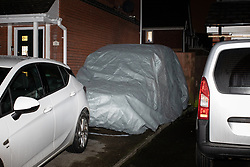 © Licensed to London News Pictures. 25/01/2020. Manchester, UK. A vehicle , believed to be a hearse , covered in a tarpaulin , on the front drive of a house on Capricorn Road in Blackley , North Manchester , which is being guarded by police . It's reported locally that a man was arrested early this morning , forensic examiners were seen entering and leaving the house and that several coffins were removed from the house during the course of the day . A Pearson's Funeral van is also reported to have been removed by police during the course of the day . Photo credit: Joel Goodman/LNP