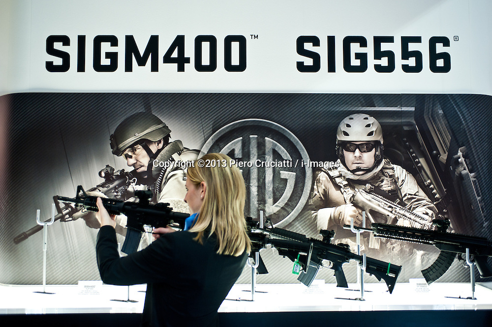 DSEI arms fair in London.<br /> A woman tries one of the arms on display during the 2013 edition of DSEI at Excel London, United Kingdom. Tuesday, 10th September 2013. Picture by Piero Cruciatti / i-Images