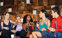 Group of friends talking sitting on couch in bar