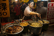 Vendors prepare food for sale at the LongShan night market in Teipei, Taiwan.