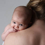 A three month old baby girl on the shoulder of her mother. Photo Tim Clayton