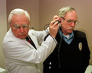 Pete Cyphers, right, has a video camera placed into his ear by Dr. Woodrow B. Kessler, left, at the TDx MacDade Mall Medical Center in Holmes, Pa., Monday, March 21, 1999, as Kessler looks at the video image on the television monitor. The video image of Cyphers' ear, is then sent via phone line to Kessler's Wallingford, Pa., office where his son Dr. Rex Kessler, not shown, views the image to consult on the examination. Woodrow says the technology he is using is invaluable to doctors looking for consults on patients all over the world.  (photo by William Thomas Cain)