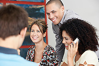 Smiling Businesspeople listening to colleague in meeting  Using Cell Phone in Meeting