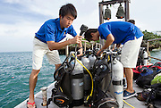 ANA InterContinental Manza Beach Resort staff helping with the the Team Tyura Sango coral restoration project check dive gear to be used on a coral planting expedition on the jetty outside the hotel in Onna Village, Okinawa Prefecture, Japan, on Saturday, June 23, 2012. Photographer: Robert Gilhooly