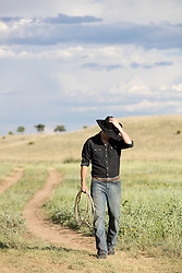 cowboy walking down a dirt path on a ranch