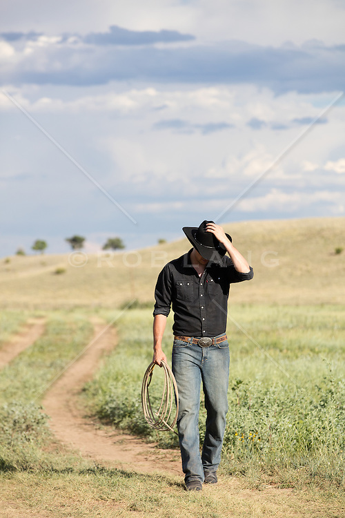 cowboy walking down a dirt path on a ranch