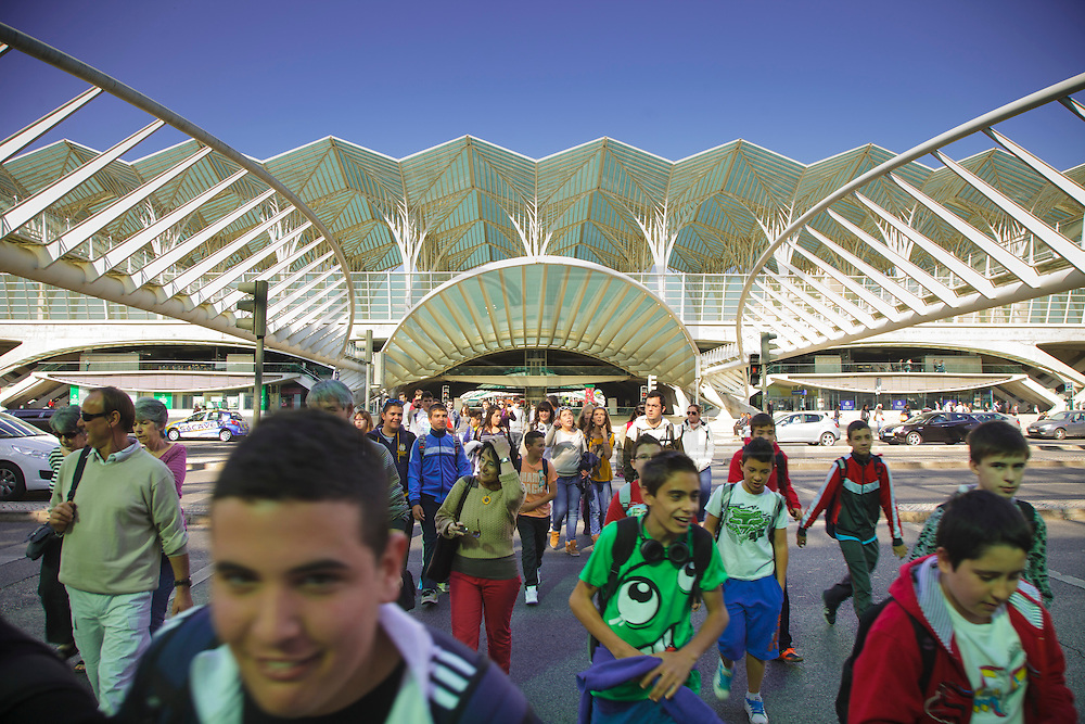 Children passing with Oriente Station in the background. The station was projected by spanish architect Santiago Calatrava and was inaugurated for the Expo98 world exhibition in Lisbon.