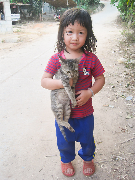 This is Mida's cousin, and her cat, Ploykwan. Ploykwan is two years old. The road behind Ploykwan in Mida's village, Mae Sa Pauk Village.