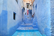 Narrow stepped street painted blue in the medina or old town of Chefchaouen in the Rif mountains of North West Morocco. Chefchaouen was founded in 1471 by Moulay Ali Ben Moussa Ben Rashid El Alami to house the muslims expelled from Andalusia. It is famous for its blue painted houses, originated by the Jewish community, and is listed by UNESCO under the Intangible Cultural Heritage of Humanity. Picture by Manuel Cohen