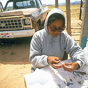 December morning on the Navajo Reservation a Navajo woman is beading necklace for the tourist at road side stand on their way to Monument Valley UT. Her husband and children are in pickup truck behind.