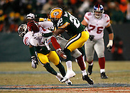 GREEN BAY,  WI - JANUARY 20:  Plaxico Burress #17 of  the New York Giants catches a pass as he collides with Atari Bigby #20 of the Green Bay Packers at the NFC Championship  game at Lambeau Field on January 20, 2008 in Green Bay, Wisconsin. The Giants defeated the Packers in overtime 23-20. Photo by Tom Hauck.