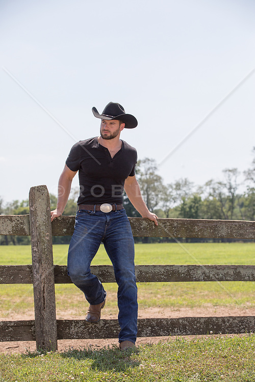 rugged cowboy by a spilt rail fence