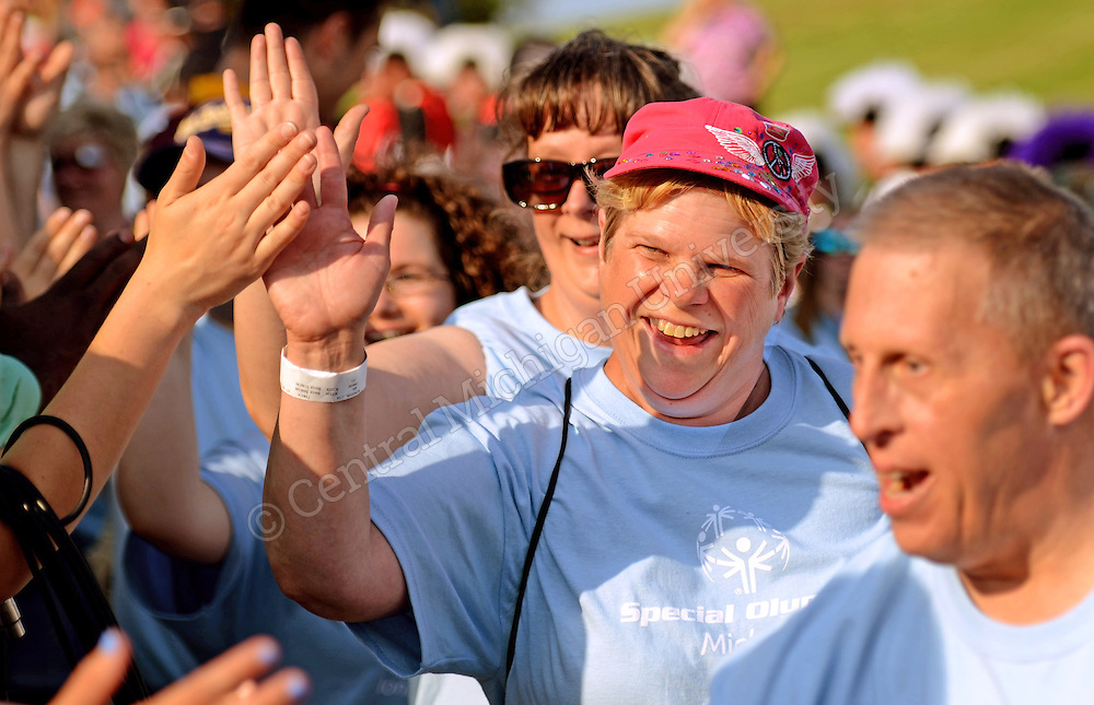 A special olympian high fives people as she enters the field during the 2015 Michigan Summer Special Olympics photo by Claire Abendroth