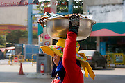 A woman is carrying a bowl containing grilled meat on top of her head on a city street in Kampong Cham, Cambodia.