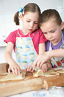 Two girls (5-6) cutting dough in kitchen
