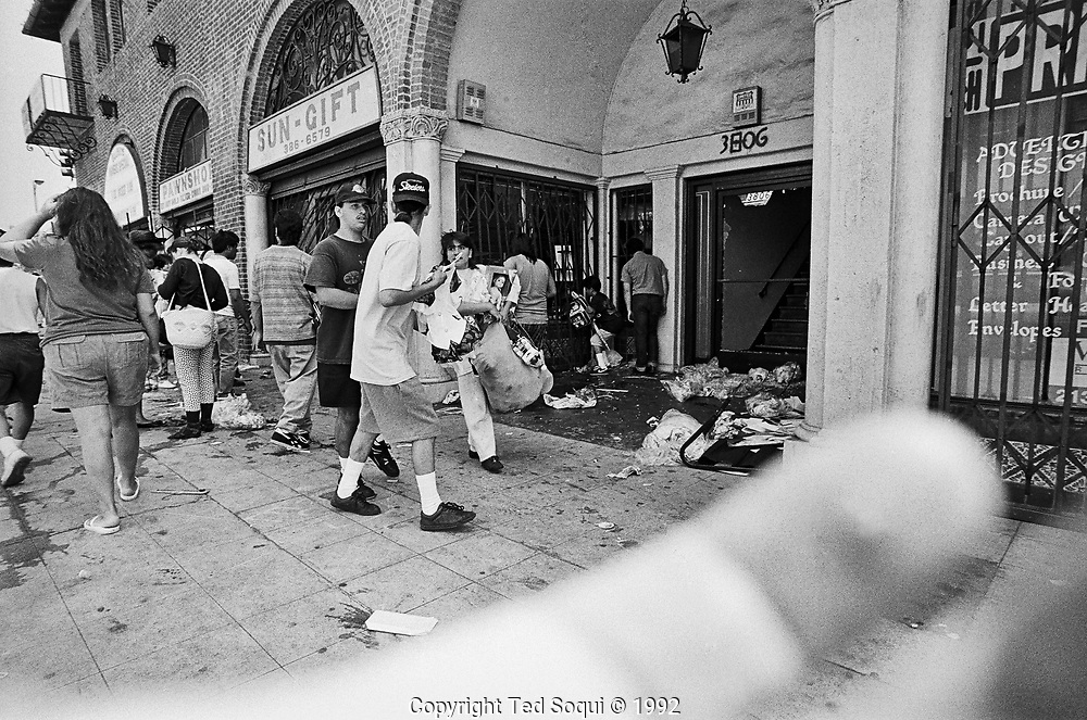 Looting on Beverly Blvd. and Vermont Ave. My fingers are in the foreground of the photo. Was using a paper bag with a hole in it to disguise my camera from looters.