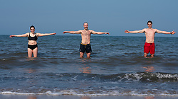 Portobello, Scotland, UK. 25 April 2020. Views of people outdoors on Saturday afternoon on the beach and promenade at Portobello, Edinburgh. Good weather has brought more people outdoors walking and cycling. The beach appears busy with possibly a breakdown in social distancing happening later in the afternoon. Three open water swimmers demonstrate social distancing in the sea. Iain Masterton/Alamy Live News
