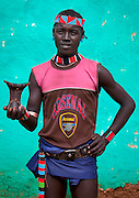 The football stars of tomorrow<br /> <br /> Thousands of Football shirts of Arsenal, Manchester, Chelsea, Milano, etc end up their carreer in... Ethiopia. Sold in the deep south, in the Omo Valley, those second hand clothes are bought by the local tribes. Most of them ignore the meaning of those shirts, and just buy them for the color, the logo, or the shape.<br /> No warrior will go out without his little pillow/seat.<br /> Some, like in Hamer tribe wear at the top of the head a clay helmet where they can put some ostrich feathers when they make a special action, like killing a wild animal, or...a man.<br /> Those tribes won't exist in few years as the ethiopian governement has launched a huge plan to develop the area.<br /> Soon, a highway coming from Mombassa - Nairobi will pass thru the villages to reach Addis Ababa.<br /> <br /> Photo shows: Bana tribe- Arsenal<br /> ©Eric Lafforgue/Exclusivepix Media