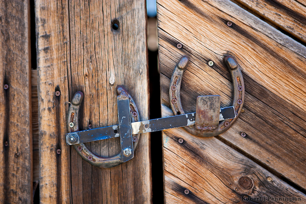 Western barn door with homemade latch made out from old horseshoes.