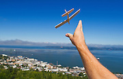 A man throws an airplane from the observation deck of the Astoria Column that overlooks the town of Astoria, Oregon in August of 2013.