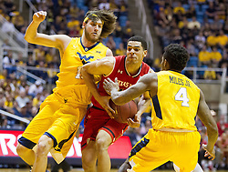 Feb 18, 2017; Morgantown, WV, USA; Texas Tech Red Raiders forward Zach Smith (11) drives while guarded by West Virginia Mountaineers forward Nathan Adrian (11) and West Virginia Mountaineers guard Daxter Miles Jr. (4) during the first half at WVU Coliseum. Mandatory Credit: Ben Queen-USA TODAY Sports