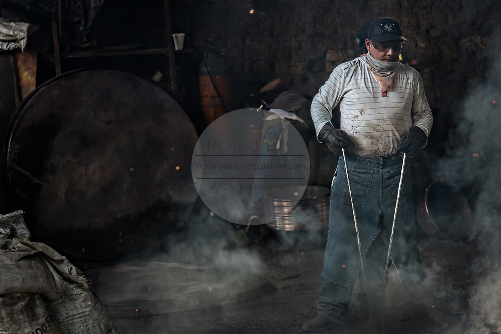 An indigenous Purepecha worker works a copper pan on an open forge to begin the process of hardening and forming the pan at a copper workshop in Santa Clara del Cobre, Michoacan, Mexico. The Purepecha people have been crafting copper crafts since the 12th century.
