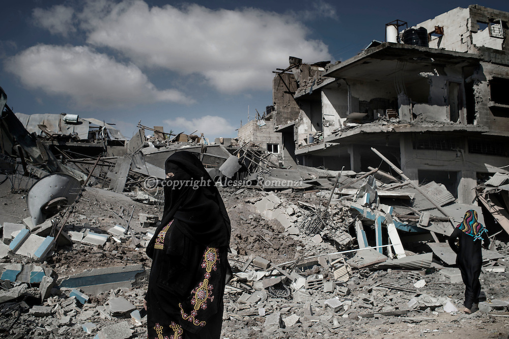 Gaza Strip, Beit Hanoun: A Palestinian woman walks by a destroyed house in the town of Beit Hanoun, during the ceasefire on July 26, 2014. ALESSIO ROMENZI