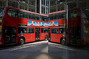 City street corner plate glass reflection of red double-decker London bus.