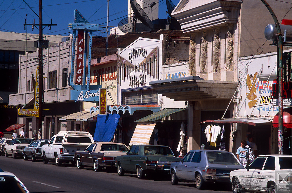 Street with shops along it, cars lining street, Nogales, Sonora, Mexico..©1990 Edward McCain. All rights reserved. McCain Photography, McCain Creative, Inc.