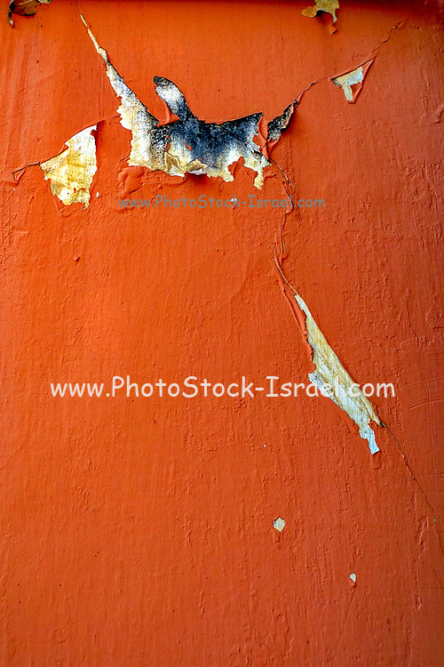 Paint and plaster peels of an orange wall