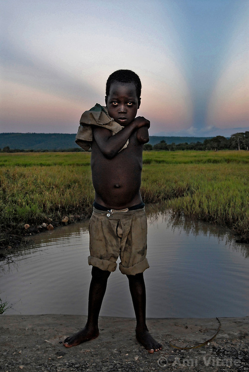 Hassan Dadi, who lost his arm after a lion ripped it off plays with his friends near a swimming hole inthe village of Usuru, Tanzania. Ami Vitale