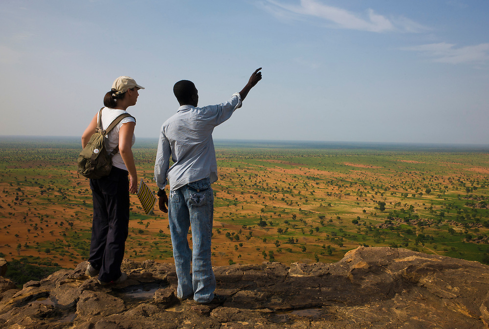 Guide Foussani Guindo explains the geology of the Bandiagara Escarpment to a tourist. The Dogon Country is the most visited part of Mali with tourists visiting its tipical  villages that can be located on the cliff, on the sandy plain or in the rocky plateau