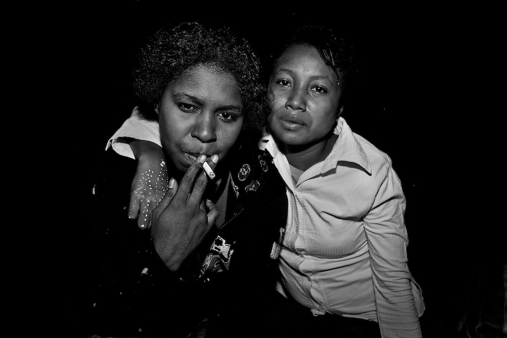 Street prostitutes, Betrix (25) and Natalia (16), both HIV positive shares a cigarette as they wait for potential clients in the capitol of Papua, Jayapura.