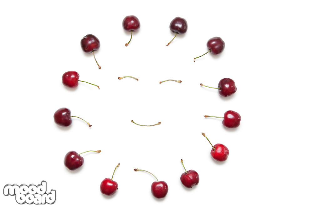 Cherries surrounding smiley face made by stems on white background