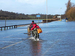 Residents make their way home along the flooded Windsor Road in Egham, United Kingdom. Saturday, 8th February 2014. Picture by Max Nash / i-Images