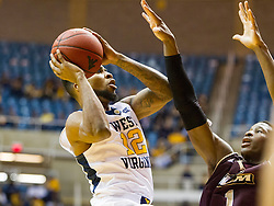 Dec 13, 2015; Morgantown, WV, USA; West Virginia Mountaineers guard Tarik Phillip (12) shoots over Louisiana Monroe Warhawks forward Travis Munnings (1) during the first half at WVU Coliseum. Mandatory Credit: Ben Queen-USA TODAY Sports