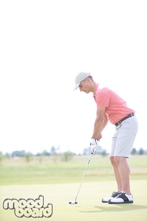 Side view of middle-aged man playing golf at course