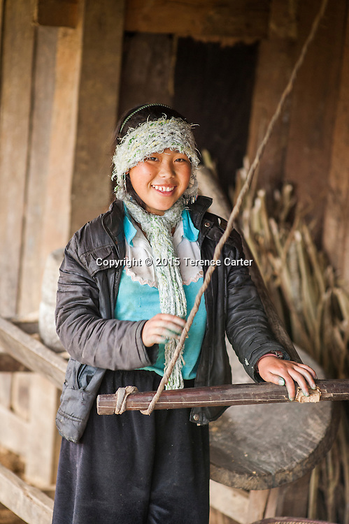 A hilltribe girl grinds flour outside her home in the hills above Sapa, Vietnam.