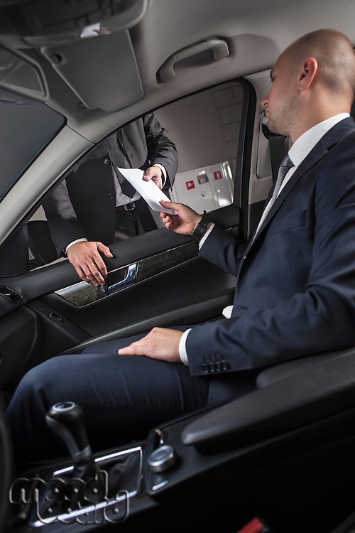 Young businessmen giving and receiving envelop through car window