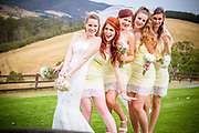 Bride and Bridesmaids in a line hold bouquets laughing and smiling