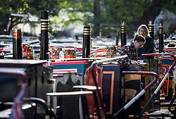 © Licensed to London News Pictures. 04/05/2019. London, UK. Boat owners surface at early morning during the Canalway Cavalcade festival in Little Venice, West London on Saturday, May 4th 2019. Inland Waterways Association's annual gathering of canal boats brings around 130 decorated boats together in Little Venice's canals on May bank holiday weekend. Photo credit: Ben Cawthra/LNP