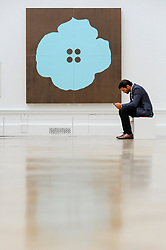 &copy; Licensed to London News Pictures. 08/06/2017. London, UK. A visitor sits in front of &quot;Aqua Button Flower June 30 2015&quot; by Donald Sultan.  Preview of the Summer Exhibition 2017 at the Royal Academy of Arts in Piccadilly.  Co-ordinated by Royal Academician Eileen Cooper, the 249th Summer Exhibition is the world's largest open submission exhibition with around 1,100 works on display by high profile and up and coming artists.<br />  Photo credit : Stephen Chung/LNP