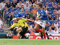 Gavin McCann (Villa) tries to stop Patrik Berger (Portsmouth) by pulling his shorts. Portsmouth v Aston Villa. 16/8/2003. Credit : Colorsport/Andrew Cowie.