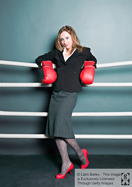 Woman in business suit and with boxer gloves